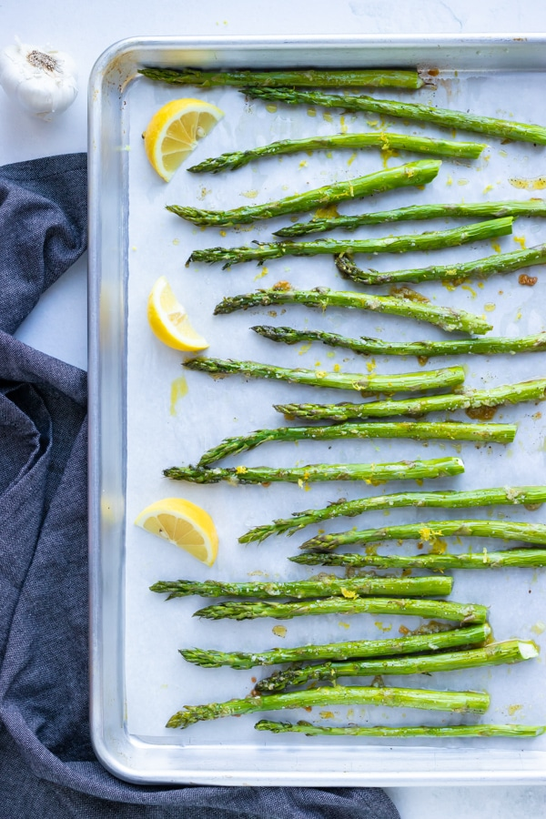 Asparagus that has been roasted in the oven on a baking sheet with lemon wedges.