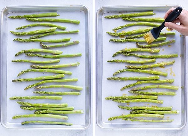 A large baking sheet with asparagus spears in a single layer and olive oil being brushed over each one.