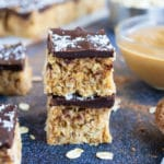 Two no-bake Samoa bars that are made with gluten-free oats, vegan shredded coconut, and peanut butter.
