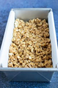 A loaf pan lined with parchment paper and full of a no-bake oatmeal bar mixture.