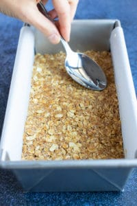 A spoon pressing down the oatmeal crumble to form the base of Samoa bars in a loaf pan.