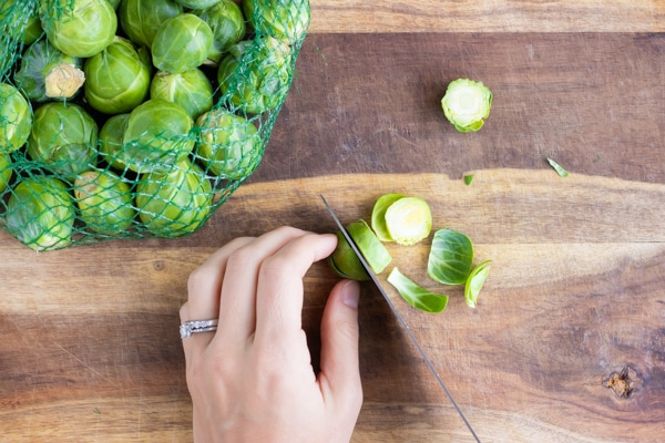 Trimming and slicing a Brussels sprout on a wooden cutting board.