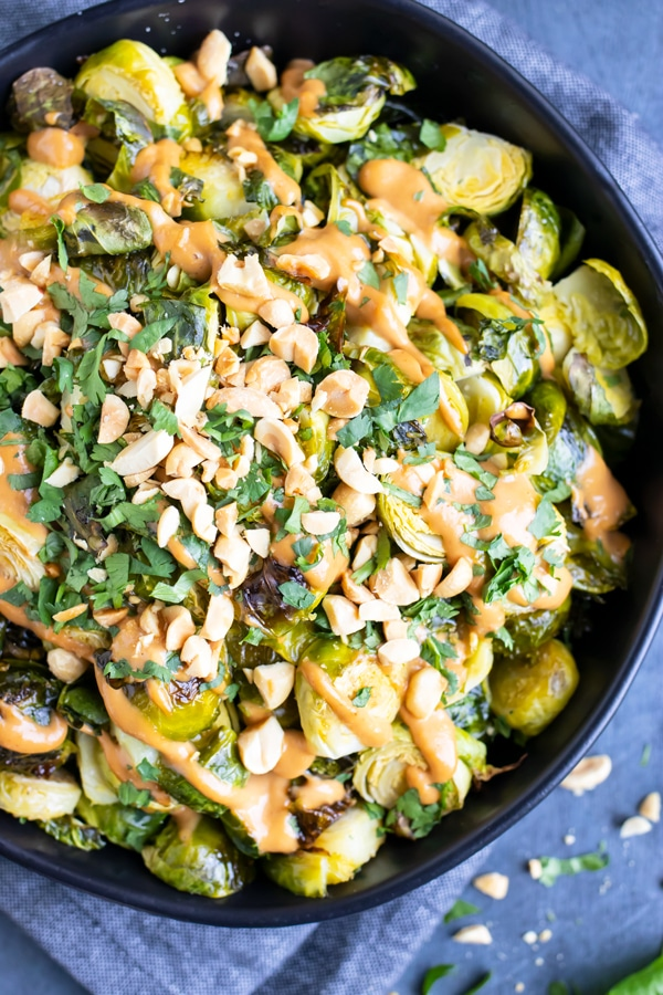 A bowl full of roasted Brussels sprouts with a peanut butter sauce and cilantro.