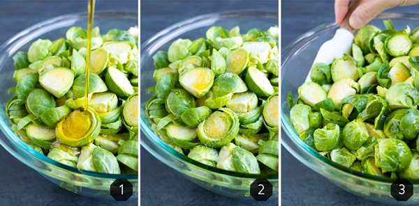 Olive oil being drizzled into a bowl full of sliced Brussels sprouts that are then tossed with a spatula.