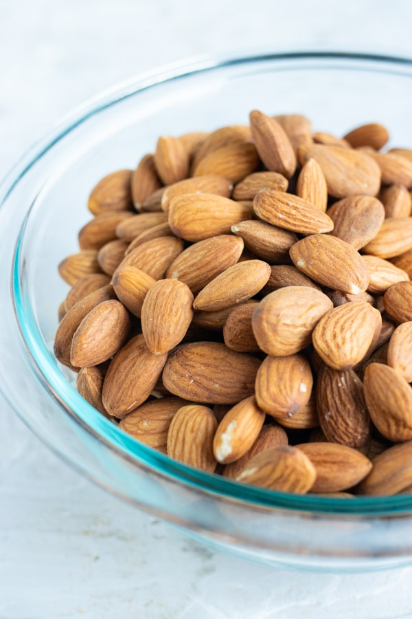 Whole toasted almonds sit in a glass bowl.