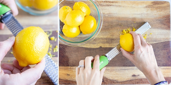 A hand moving a lemon back and forth over a microplane.