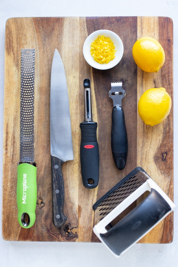 A microplane, knife, vegetable peeler, citrus zester, cheese grater, lemons and zest on a wooden cutting board.