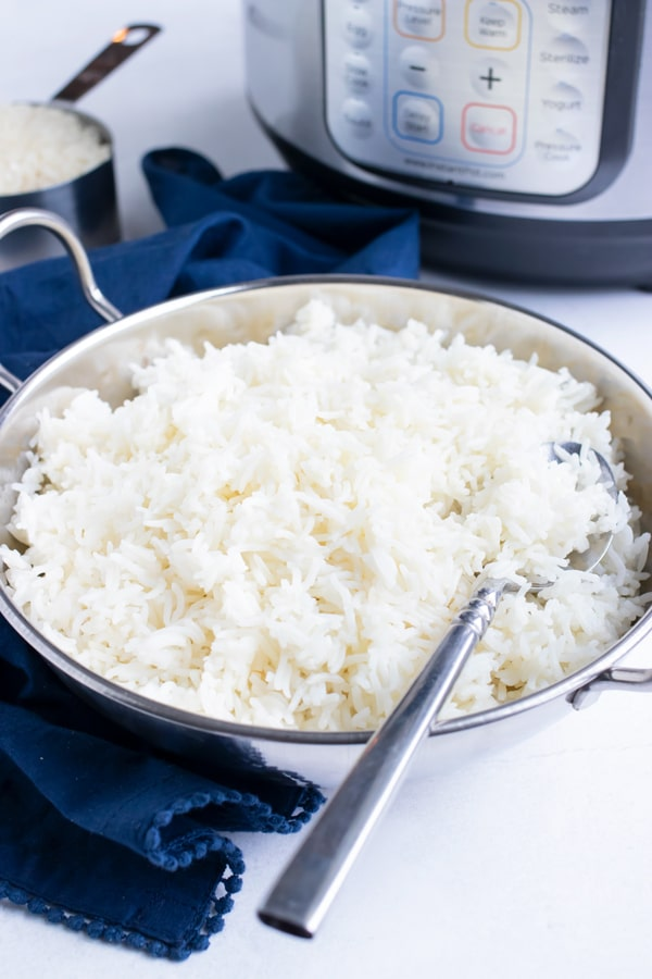 An Indian silver metal serving bowl full of basmati rice with an Instant Pot.
