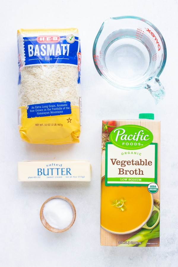 Dried rice, water, butter, and salt as the ingredients for a basmati rice recipe.