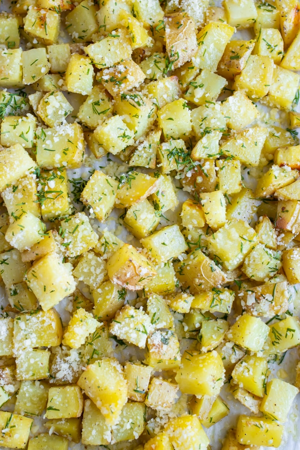 Lemon Dill roasted potatoes with Parmesan cheese on a large baking sheet.