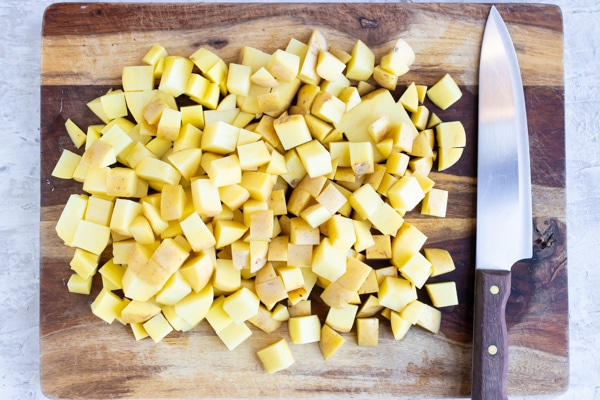 A wooden cutting board with cubed Yukon gold potatoes next to a chef's knife.