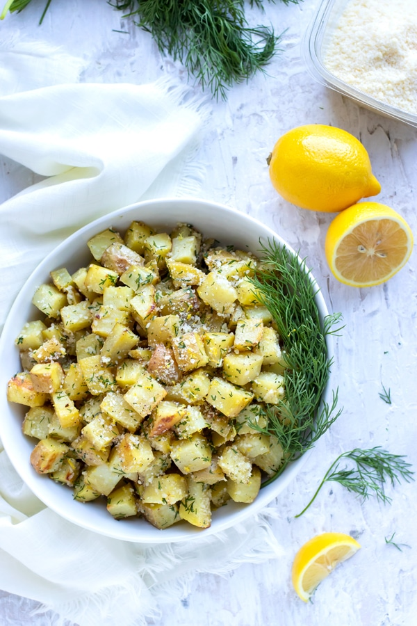 A bowl full of a potato side dish recipe next to lemons, Parmesan cheese, and fresh dill.