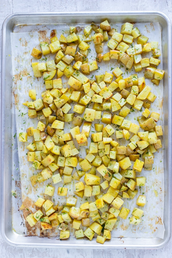 Roasted cubed potatoes on a parchment paper lined baking sheet.
