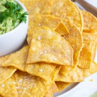 Homemade tortilla chips on a white plate next to a bowl of guacamole.
