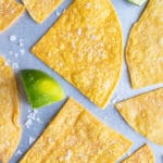 A baking sheet with homemade tortilla chips in a single layer with salt and limes.