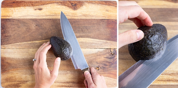 A knife cutting an avocado in half lengthwise.
