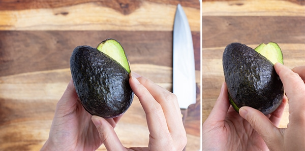 Two halves of an avocado being twisted in opposing directions.