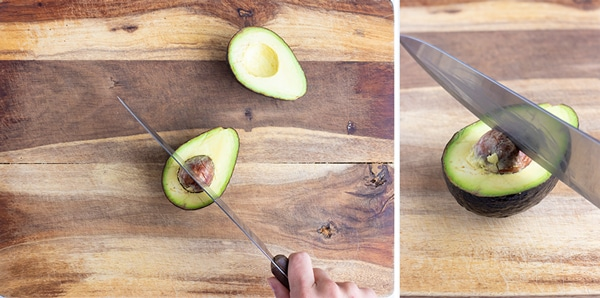 A chef's knife hitting an avocado pit to remove it.