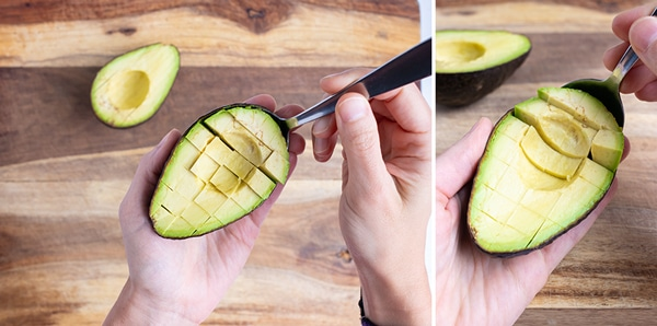 A spoon scooping out cubes of avocado from the peel.