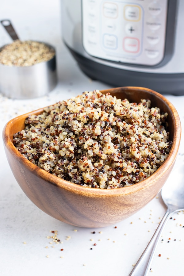 A wooden bowl full of cooked tri-color quinoa with an Instant Pot.