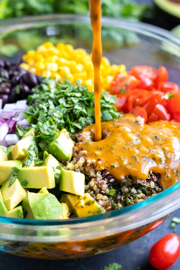 Homemade cilantro lime dressing being poured into a quinoa salad.