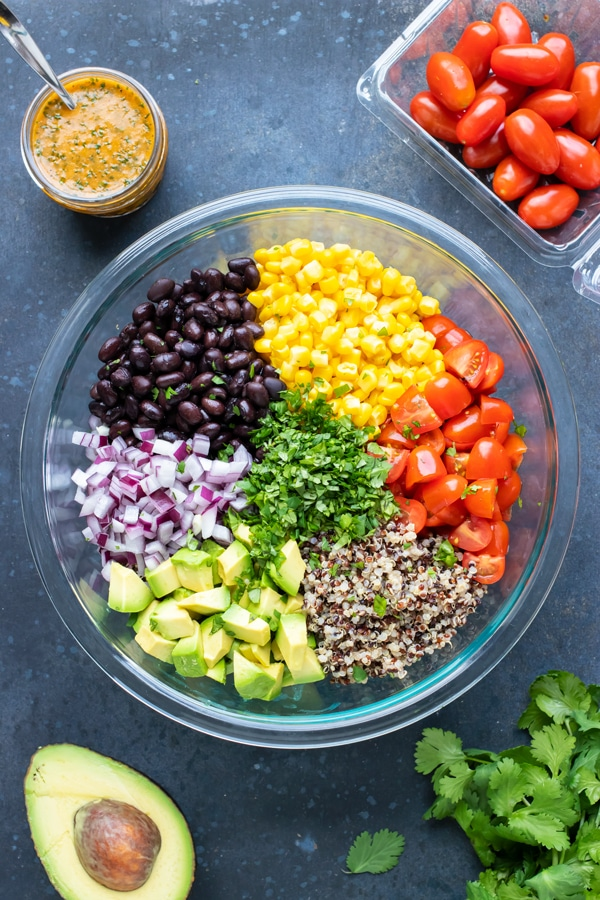 A glass bowl full of black beans, corn, tomatoes, quinoa, avocado, and red onions.