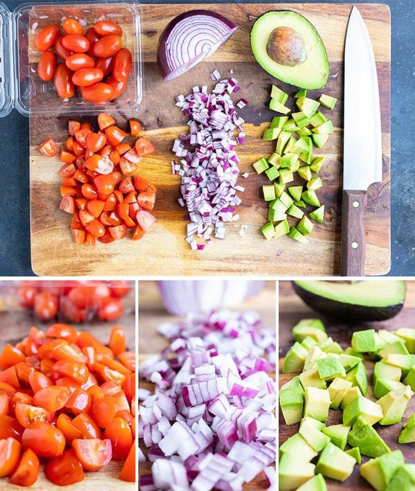 Chopped tomatoes, red onion, and avocado on a wooden cutting board.