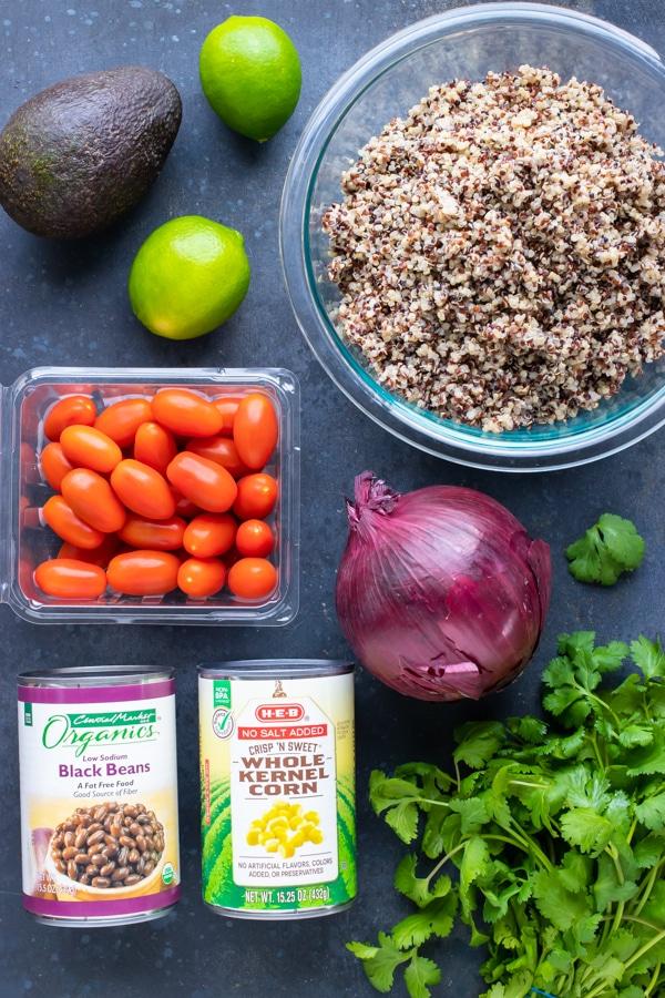 Cooked quinoa, avocado, tomatoes, beans, corn, and cilantro for a salad recipe.