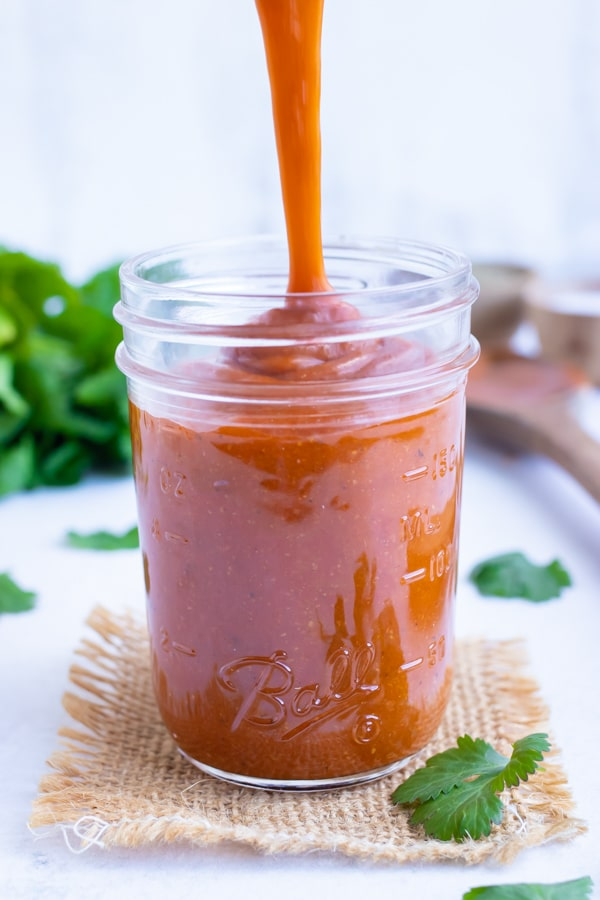 Red enchilada sauce being poured into a glass mason jar to be stored in the refrigerator for a week.