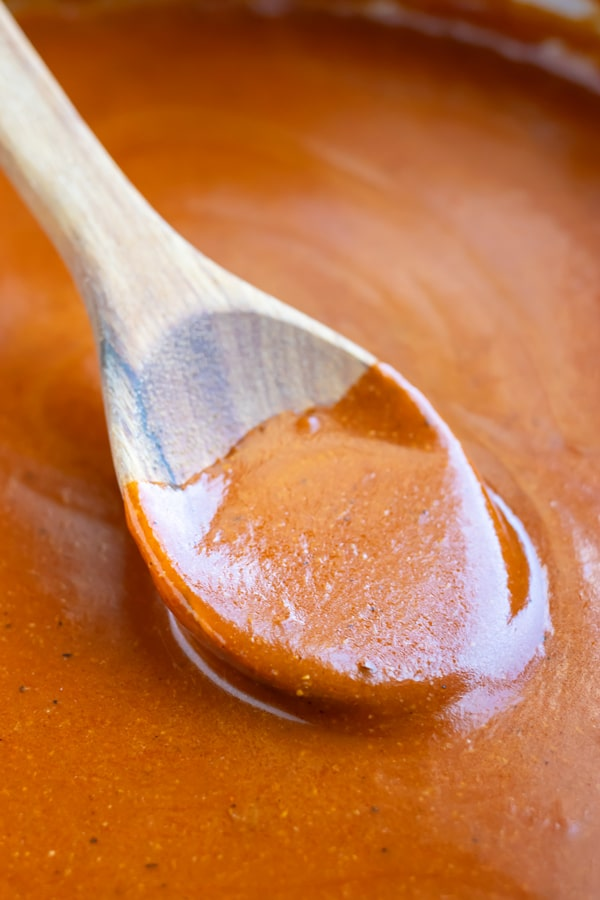 A wooden spoon stirring a red enchilada sauce.