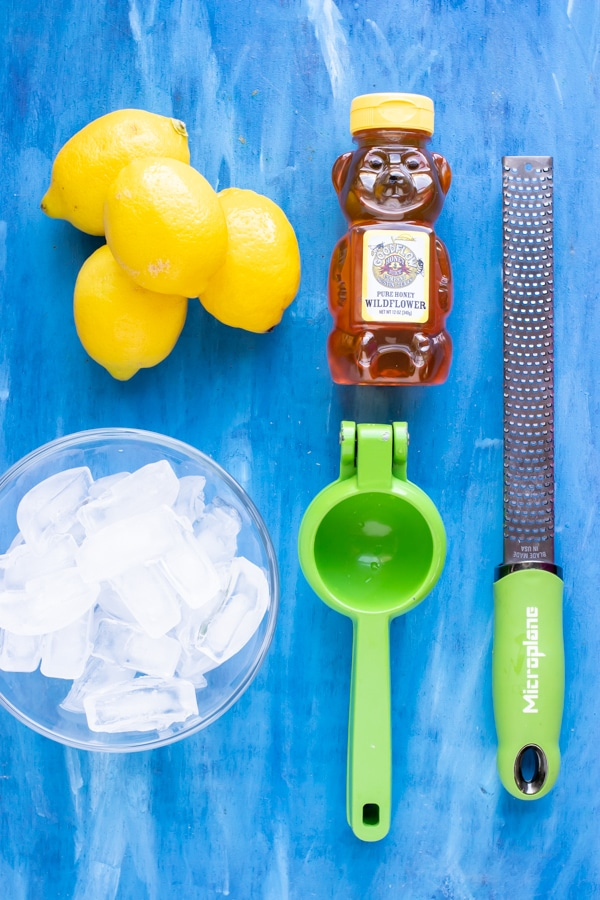 Lemons, honey, and ice as the ingredients for an easy frozen lemonade recipe.