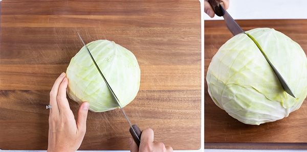 A head of cabbage with the stem side down on a cutting board being cut in half lengthwise.