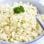Instant couscous in a grey bowl with parsley sprinkled on top.