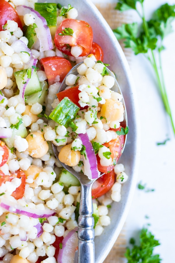 A spoon scooping out a bite of a cold Mediterranean couscous salad from a bowl.