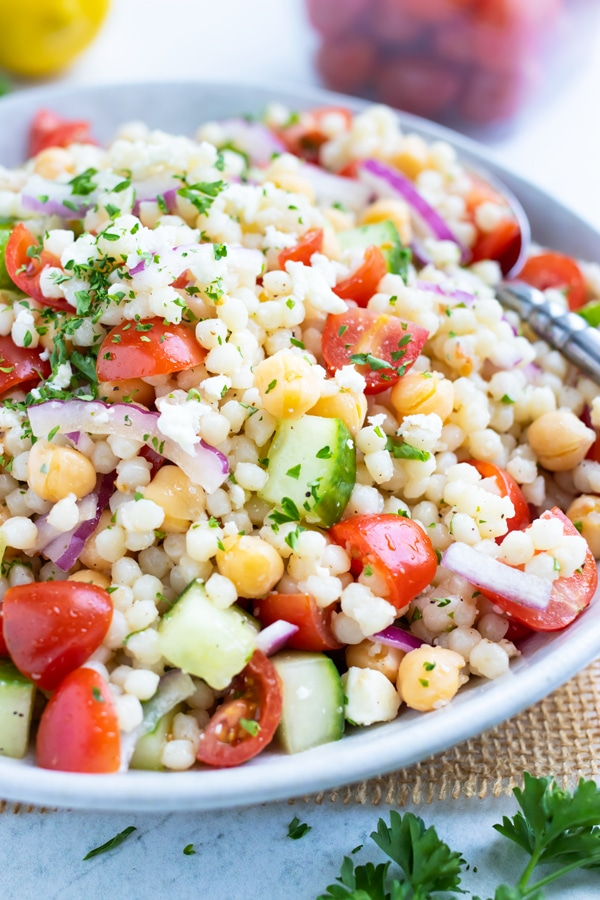 A cold summer salad made with couscous, cucumbers, tomatoes, and Greek flavors.