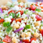 A big glass bowl full of a Mediterranean Couscous Salad with tomatoes, feta, garbanzo beans, and cucumbers.