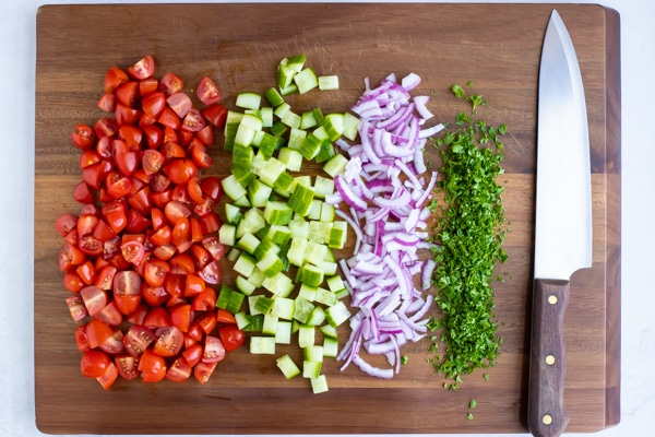 Finely diced red onion, chopped parsley, diced cucumbers, and chopped cherry tomatoes on a wooden cutting board.