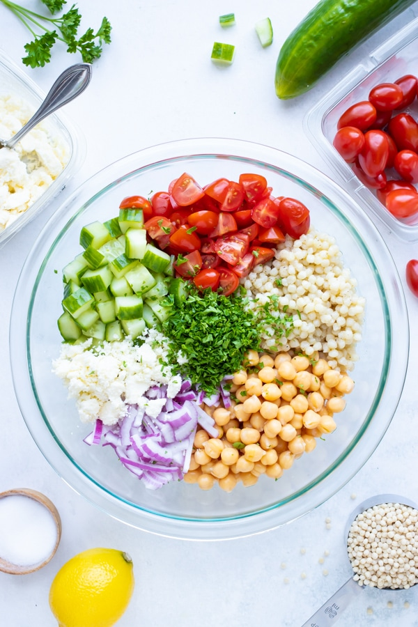 A large mixing bowl with pearl couscous, garbanzo beans, tomatoes, cucumbers, and chopped parsley.