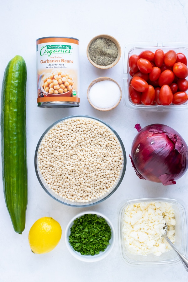 Cucumber, garbanzo beans, couscous, tomatoes, onion, feta, parsley, and lemon as ingredients for a recipe.