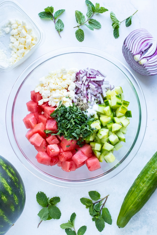 A clear glass mixing bowl full of cubed watermelon, feta cheese crumbles, red onion, cucumbers, and chopped sweet mint.