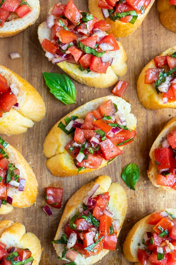 An easy fresh tomato bruschetta on top of toasted baguette bread on a wooden appetizer tray.