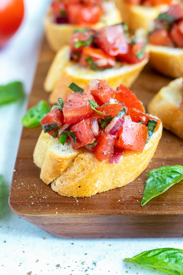 Toasted baguette bread with an Italian bruschetta topping and a leaf of basil on an appetizer tray.
