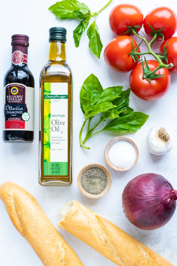 Campari vine-ripened tomatoes, olive oil, basil, balsamic vinegar, onion, and bread as the ingredients for an easy homemade bruschetta recipe.