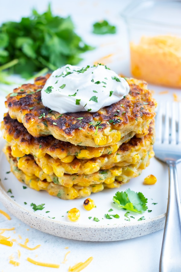 Southern Fried Corn Fritters with a tub of shredded cheddar cheese and cilantro behind them.