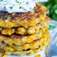 A stack of cheesy corn fritters with a dollop of sour cream and cilantro in the background.