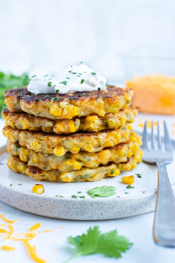 An appetizer plate with easy Southern corn fritters in a stack with fresh cilantro.