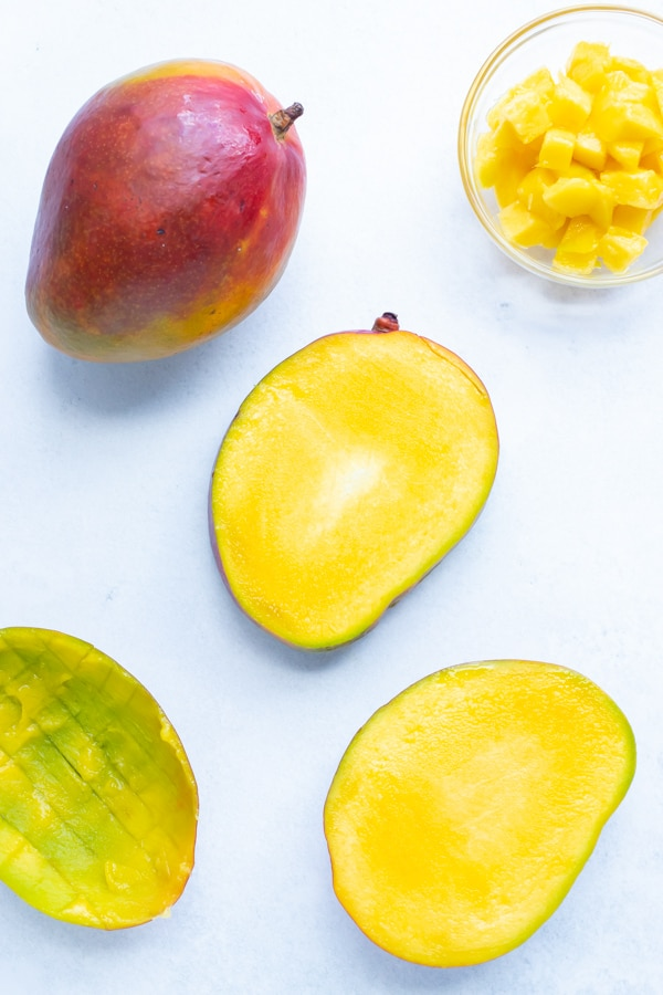 A whole mango, a piece of mango with the pit and stem, and a slice of mango cheek.