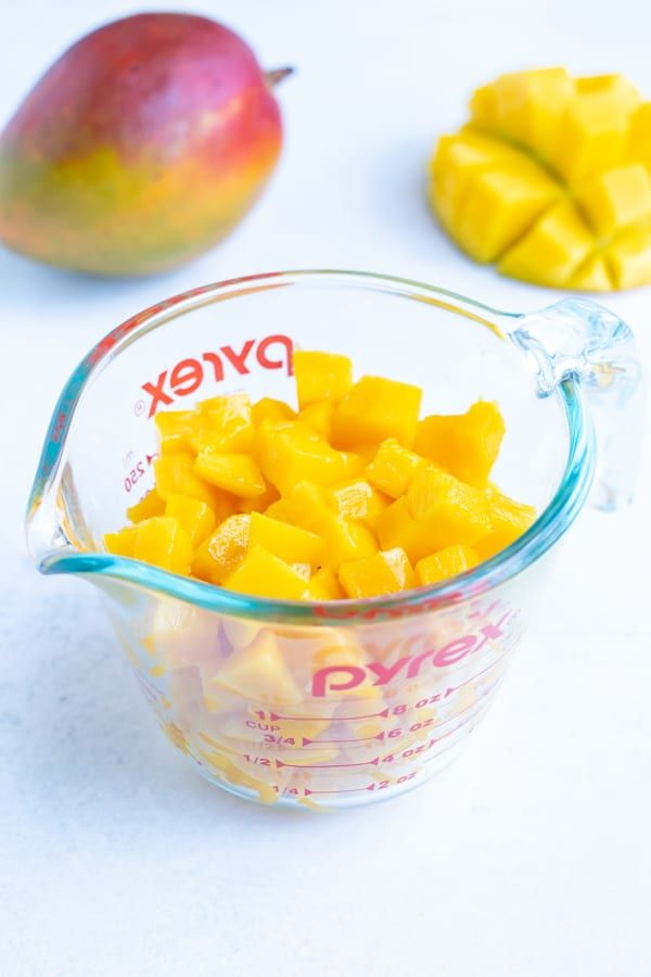 A measuring cup full of freshly cut mango showing that one medium mango equals roughly 1 1/2 cups of fruit.