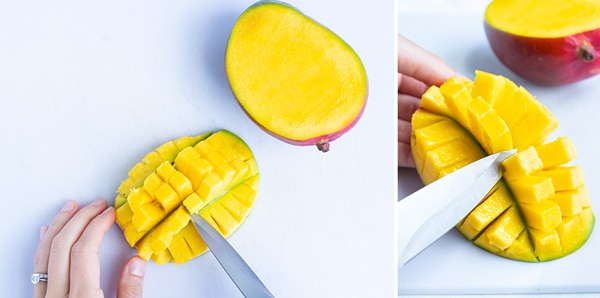 Using a knife to cut diced mango from the skin.