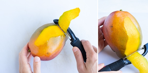 Using a vegetable peeler to peel a mango before cutting, slicing, or dicing.